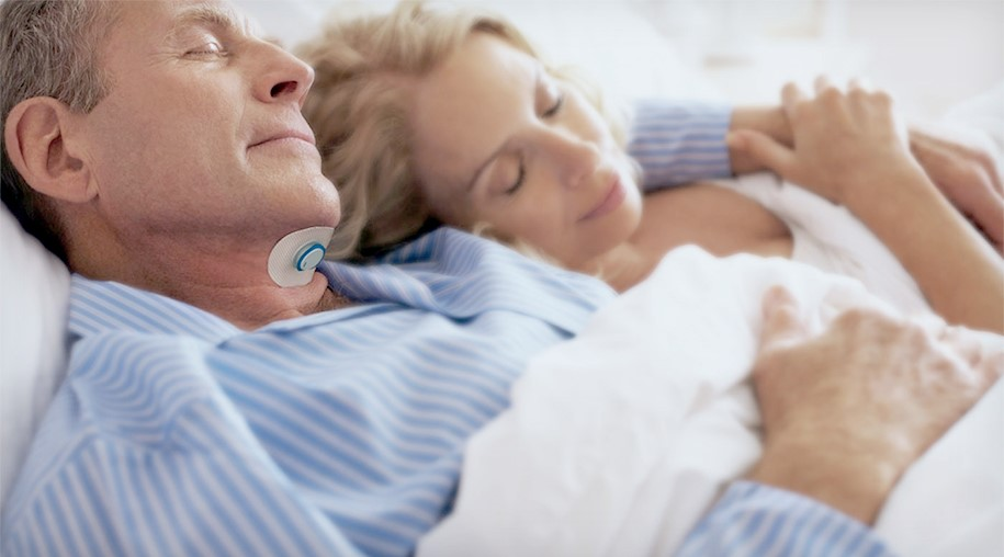 A couple sleeps peacefully. The man is wearing a medical patch device on his throat